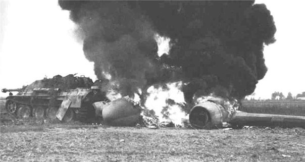 """Подбитая немецкая противотанковая Сау """"Ягдпантера"""". Сзади самоходки взорвавшийся и горящий самолёт"""
